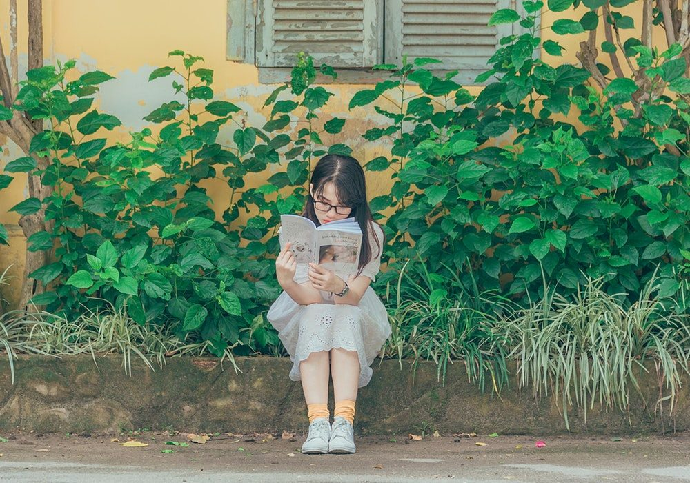 Child wearing glasses and reading a book